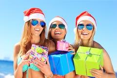 Groupe de filles dans des chapeaux de Santa ayant l'amusement sur la plage Photos stock