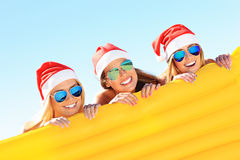 Groupe de filles dans des chapeaux de Santa ayant l'amusement sur la plage Image libre de droits