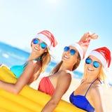Groupe de filles dans des chapeaux de Santa ayant l'amusement sur la plage Images stock