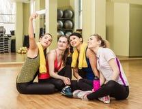 Groupe de filles dans la classe de forme physique faisant le selfi Image stock