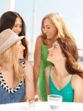 Groupe de filles de sourire en café sur la plage Photos libres de droits