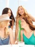 Groupe de filles de sourire en café sur la plage Photos stock