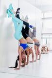 Groupe de filles de sourire sportives se tenant sur des mains se penchant contre le yoga de pratique de mur dans le studio de for Images stock