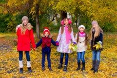 Groupe de filles en parc d'automne avec des feuilles Photographie stock