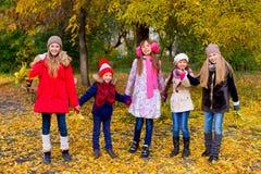 Groupe de filles en parc d'automne avec des feuilles Image libre de droits