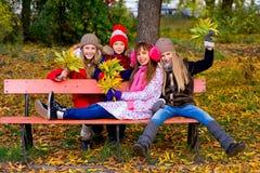 Groupe de filles en parc d'automne avec des feuilles Images stock