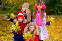 Groupe de filles en parc d'automne avec des feuilles Photographie stock libre de droits