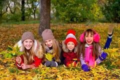 Groupe de filles en parc d'automne avec des feuilles Photos stock