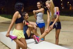 Groupe de filles faisant s'étirant la nuit Image stock