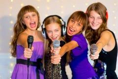 Groupe de filles heureuses chantant sur le karaoke Images libres de droits