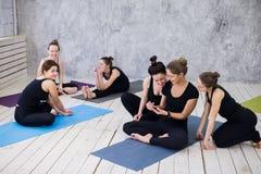 Groupe de filles heureuses dans la classe de forme physique à la coupure regardant le smartphone Images stock