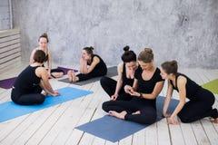 Groupe de filles heureuses dans la classe de forme physique à la coupure regardant le smartphone Image stock