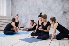 Groupe de filles heureuses dans la classe de forme physique à la coupure regardant le smartphone Photos stock