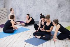 Groupe de filles heureuses dans la classe de forme physique à la coupure regardant le smartphone Photographie stock libre de droits
