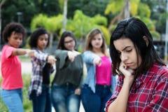 Groupe de filles intimidant une jeune femme adulte arabe photos stock