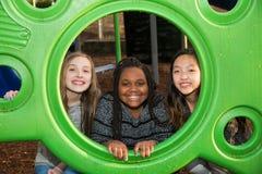 Groupe de filles jouant ensemble au terrain de jeu d'école Photo stock