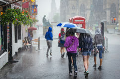 Groupe de filles marchant à la pluie d'été dans la ville photographie stock libre de droits