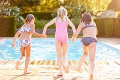 Groupe de filles sautant dans la piscine extérieure Image stock