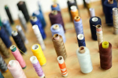 Groupe de fils de couture sur le conseil en bois Images libres de droits