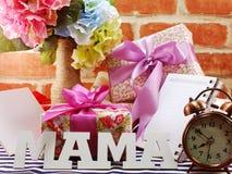 Groupe de fleurs avec un boîte-cadeau et une maman de mot sur le fond en bois Photos libres de droits