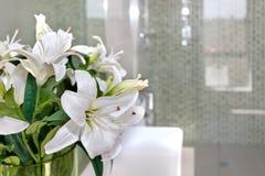 Groupe de fleurs blanches sur le verre d'une salle avec le backg brouillé Image stock