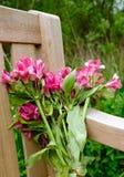 Groupe de fleurs de fanage vues à gauche sur un banc en bois dans un cimetière Photographie stock libre de droits