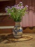 Groupe de fleurs violettes roses dans le vase peint en céramique rustique sur o images stock