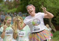 Groupe de fonctionnement, adolescents heureux et souriants couverts de coloré Photographie stock libre de droits