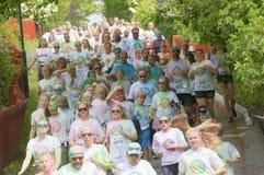 Groupe de fonctionnement, adolescents heureux et souriants couverts de coloré Photographie stock