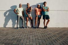 Groupe de forme physique posant par un mur dehors Images stock