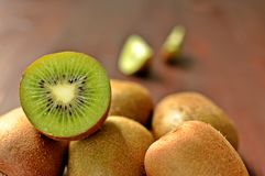 Groupe de fruit entier mûr de kiwis et de kiwi de moitié sur le fond en bois brun photos libres de droits