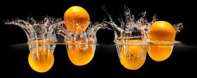 Groupe de fruits frais tombant dans l'eau avec l'éclaboussure sur le fond noir image stock