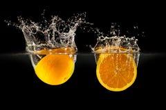 Groupe de fruits frais tombant dans l'eau avec l'éclaboussure sur le fond noir image libre de droits