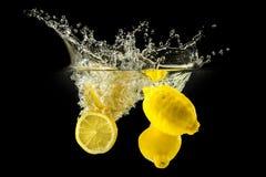 Groupe de fruits frais tombant dans l'eau avec l'éclaboussure sur le fond noir images libres de droits