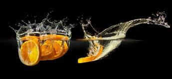 Groupe de fruits frais tombant dans l'eau avec l'éclaboussure sur le fond noir photos stock