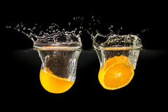 Groupe de fruits frais tombant dans l'eau avec l'éclaboussure sur le noir de retour photo libre de droits