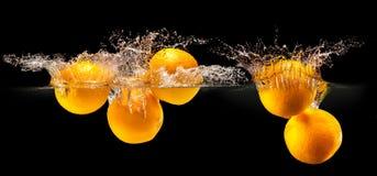 Groupe de fruits frais tombant dans l'eau avec l'éclaboussure sur le noir de retour photographie stock libre de droits