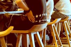 Groupe de garçon s'asseyant sur la chaise en bois Images stock