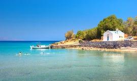 Groupe de garçons ayant l'amusement à la belle plage dans Istron, Crète Photographie stock