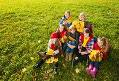 Groupe de garçons et de filles sur la pelouse d'automne Photographie stock libre de droits