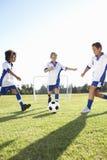 Groupe de garçons jouant le football Photographie stock libre de droits