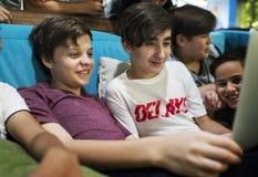 Groupe de garçons reposant l'unité et à l'aide de l'ordinateur portable Images stock