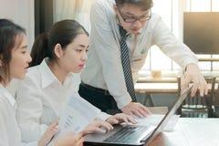 Groupe de gens d'affaires asiatiques travaillant ensemble sur un ordinateur portable au bureau Concept brainstroming de travail d Photographie stock libre de droits