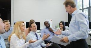 Groupe de gens d'affaires discutant des documents avec la principale présentation d'homme d'affaires lors de la réunion de format banque de vidéos