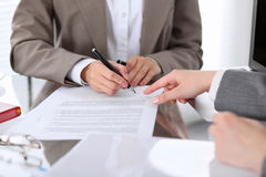 Groupe de gens d'affaires et d'avocats discutant le contrat se reposant à la table Le chef de femme signe des papiers Photos stock