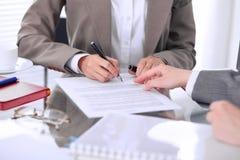Groupe de gens d'affaires et d'avocats discutant le contrat se reposant à la table Le chef de femme signe des papiers Images stock