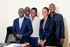 Groupe de gens d'affaires heureux posant ensemble au bureau photo stock