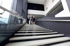 Groupe de gens d'affaires marchant aux escaliers Photo stock