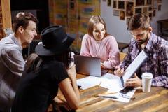 Groupe de gens d'affaires occasionnels travaillant sur le nouveau projet Ils utilisant l'ordinateur portable et discutent au suje Photographie stock libre de droits