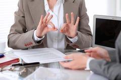 Groupe de gens d'affaires ou d'avocats lors de la réunion discutant des papiers de contrat Femme affichant le signe en bon état Image stock